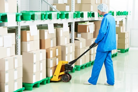pharmaceutical: medical warehouse worker man loading boxes with medcine drugs by hand forklift