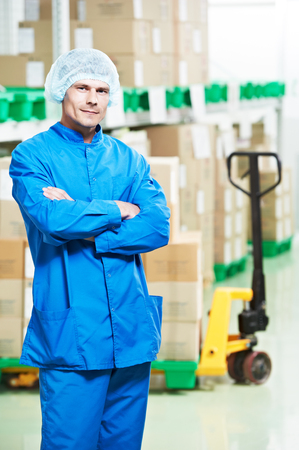 medical distribution: young handsome medical warehouse worker man in front of boxes with medcine drugs stack arrangement