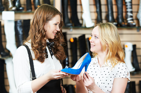 choosing: Young woman and seller assistant choosing footwear during shopping at shoe shop