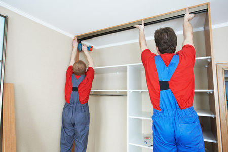 jointly: Two carpenters workers joint and settle home built-in cupboard Stock Photo