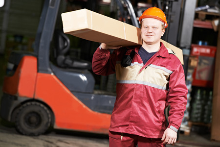 young warehouse worker in uniform in front of forklift stacker loader with box photo