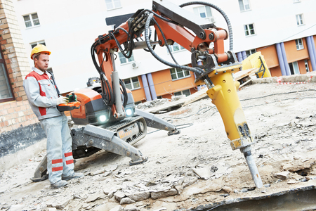 Baumeister Arbeiter in Sicherheit Schutzausrüstung Arbeitskonstruktion Abbruchmaschine Roboter. Konzentrieren Sie sich auf Werkzeug Standard-Bild