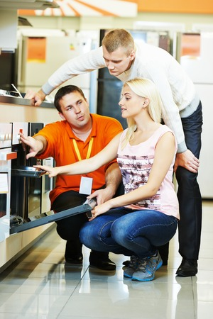 home appliance: Seller assistant demonstrating cooker stove to young family in home appliance shopping mall supermarket Stock Photo