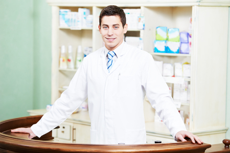 druggist: young pharmacist chemist man standing in pharmacy drugstore Stock Photo