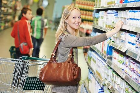 ショッピング。女を乳製品店やスーパー マーケットでバイオ食品のチーズを選ぶ
