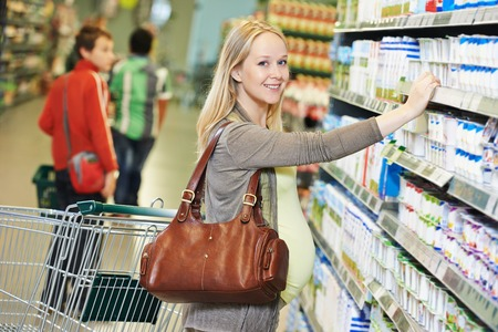 food products: Shopping. Woman choosing bio food cheese products in dairy store or supermarket Stock Photo