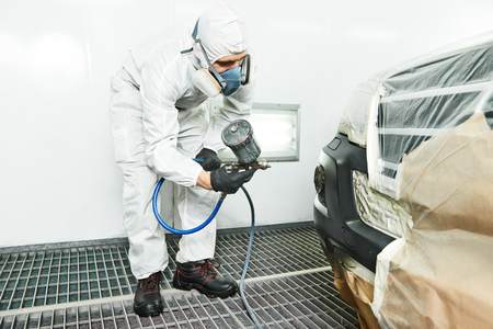 paint gun: automobile repairman painter painting car body bumper in chamber Stock Photo