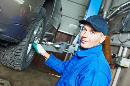 mecanico: retrato de trabajador mec�nico de autom�viles antes de reparar la suspensi�n del autom�vil levantado en reparaci�n de autom�viles estaci�n de tienda de garaje