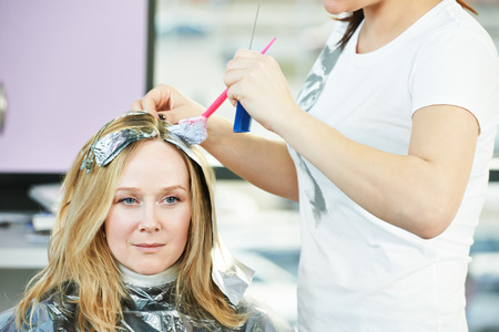 Highlight. Hairdresser woman making highlighting coloring of female client hair in beauty parlour hairdressing salon Foto de archivo