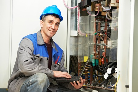 power distribution: electrician engineer inspector with computer near the fuse box Stock Photo
