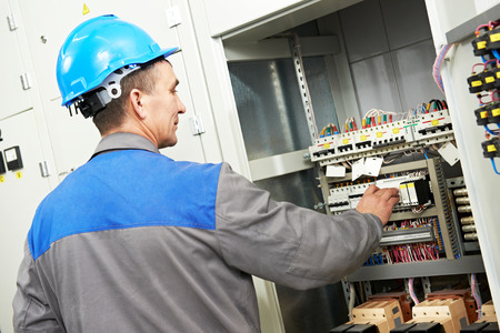 electrical contractor: electrician worker with switching on the electric power switch in fuse board Stock Photo