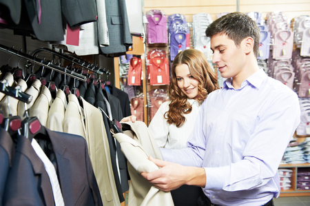 Young man and woman choosing suit jacket during apparel shopping at clothing store photo