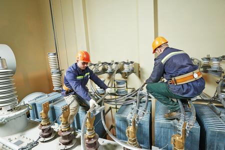 Elektriker lineman repairman Arbeiter bei großen Industriestromtransformator Installationsarbeiten