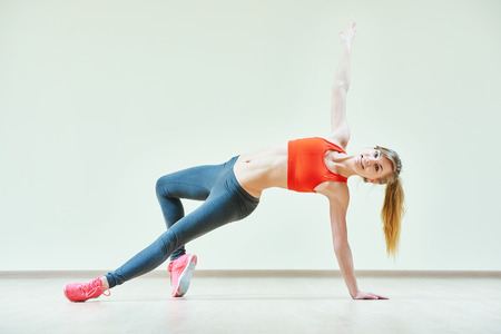 yoga class: fitness instructor doing pilates or dancing exercises in sport club