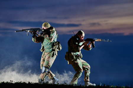 special agent: military. two soldiers in uniform running with assault rifle weapon on sunset during attack outdoors. Authentic shooting in challenging conditions. Maybe little blurred. Stock Photo