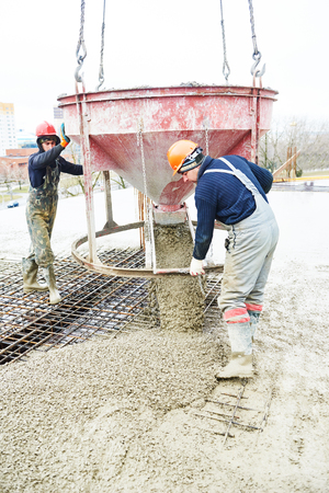 concreting: concreting work: construction site worker during concrete pouring into formwork at building area with skip