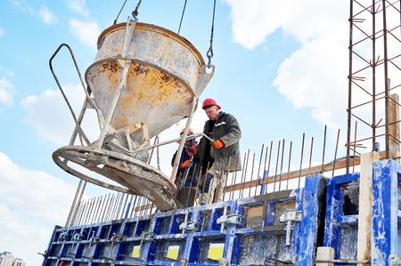 hombres trabajando: hormigonado de trabajo: trabajadores de la construcción que vierten el concreto en un encofrado en el área edificio con salto