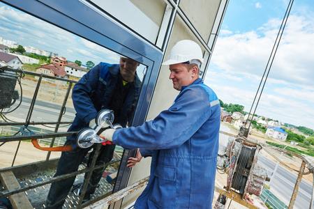 alba�il: instalaci�n de la ventana. masculina del trabajador de construcci�n industrial en la fachada de vidrio.