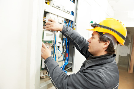 energy work: electrician builder at work installing energy saving meter into electric line distribution fuseboard
