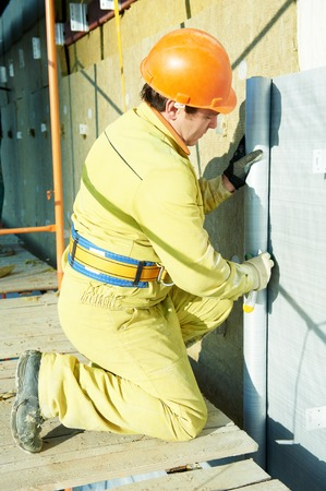 building external: facade plasterer builder at outdoor building external wall insulation with wind protection film