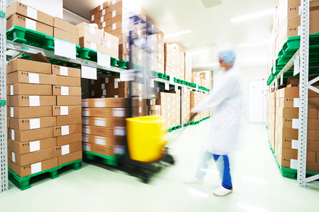 stacker: warehouse worker with stacker loader truck at work. man blurred in motion intentionally.