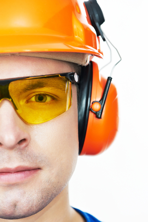 mounter: Close-up face portrait of young builder worker in protective hardhat with ear muff and protective glasses Stock Photo