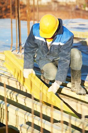 concrete form: construction worker at construction site assembling falsework for concrete pouring
