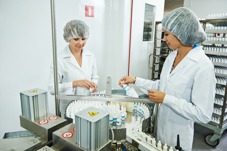 factory line: Two pharmaceutical factory workers at pharmacy industry manufacture checking medicine on conveyer Stock Photo