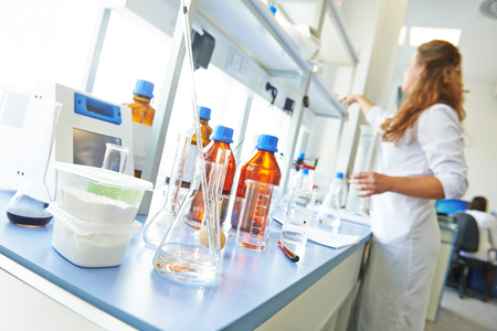 Pharmacy and chemistry theme. Container of powder and test glass flask with solution in research laboratory. Shallow DOF