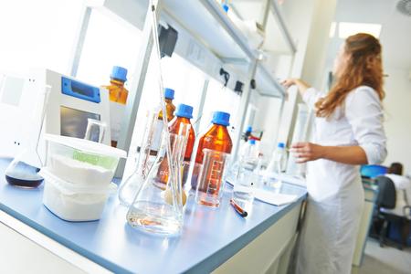 Farmacie en chemie thema. Container van poeder en test glazen kolf met een oplossing in onderzoekslaboratorium. Ondiepe DOF