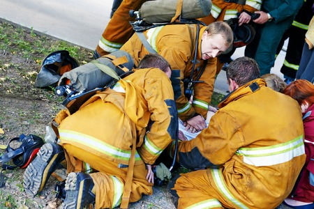 respiration: rescue operation. Team of fireman making artificial respiration to the fire victim. Authentic shot. may be little blurred Stock Photo