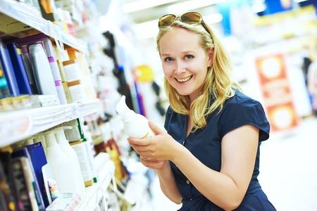 productos de aseo: Compras. Mujer que elige cuidado de la piel productos de crema cosmética en la tienda de belleza o en el supermercado. DOF bajo