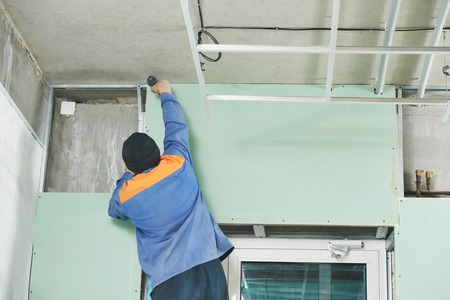 plasterboard: Carpenter joiner plasterer with screwdriver mounting gypsum plasterboard system at toilet