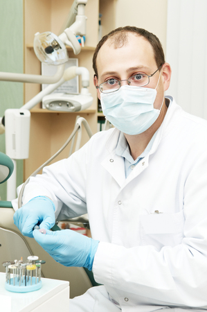 dental prophylaxis: Portrait of male dentist with mask and gloves on his working place in dental clinic
