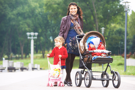 Smiling young mother walking with daughter outdoors in a spring park pushing pram. Little boy in stroller.
