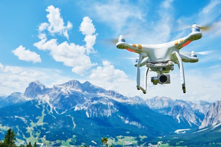 White drone quadrocopter with high resolution digital camera flying in the blue sky over the mountain