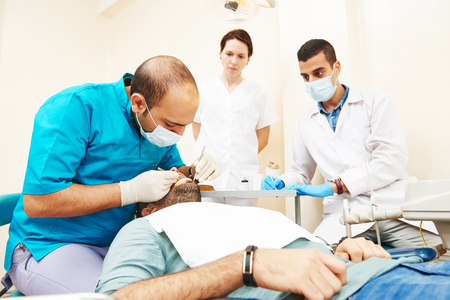 medical practice: Dentistry education. Female dentist doctor teacher explaining treatment procedure to male iranian asian students in dental clinic Stock Photo