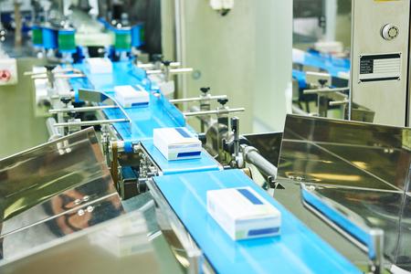 cinta transportadora: farmacéutica producción de embalaje línea transportadora en la fábrica de farmacia fabricación. Tiro Auténtico en condiciones difíciles. quizá poco borrosa