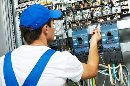 electrician worker checking voltage of the electric power switch in fuse board