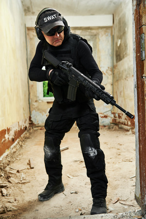 contractor: Military industry. Special forces or anti-terrorist police soldier,  private military contractor armed with pistol ready to attack during clean-up operation, mission