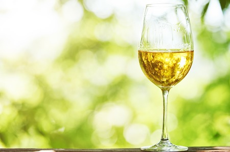 Glass of Chardonnay, Sauvignon or Rkatsiteli white wine over outdoors background
