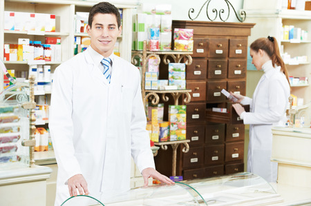 young pharmacist chemist man and woman  standing in pharmacy drugstore photo
