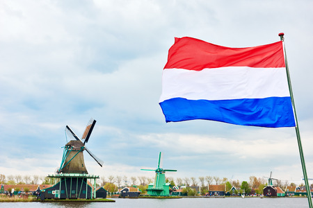 dutch windmill: Flag of the Netherlands against traditional dutch windmill near  canal in Zaanse Schans