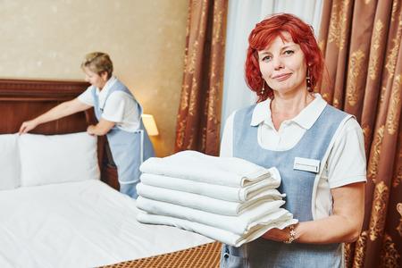mucama: El servicio del hotel. Servicio de limpieza de sexo femenino del personal con toallas en frente de la dama que hace la cama en la habitación