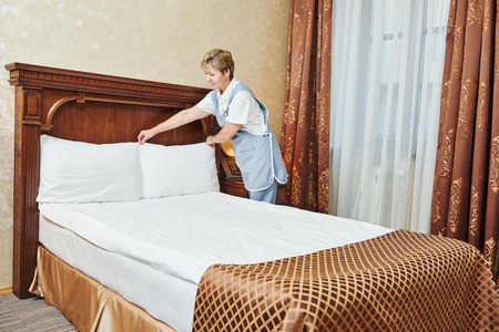 bedclothes: Hotel service. female housekeeping worker maid making bed with bedclothes at inn room Stock Photo