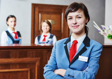 front desk: Happy young female hotel receptionist worker standing at reception