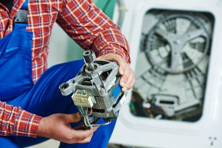 Reparación de la máquina de lavado. Manos reparador con motor eléctrico del motor en frente de la unidad dañada Foto de archivo