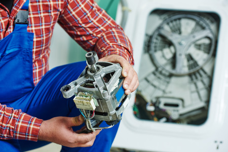 Wasmachine reparatie. Reparateur handen met elektrische motor motor voor beschadigde unit Stockfoto