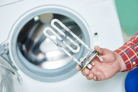 Washing machine repair. Hand of repairer with turbular electric heating element Archivio Fotografico