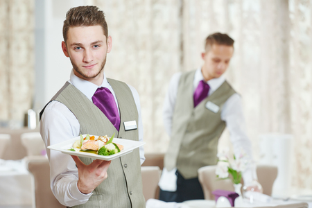 Waiter occupation. Young man with food on dishes servicing in restaurant 스톡 콘텐츠